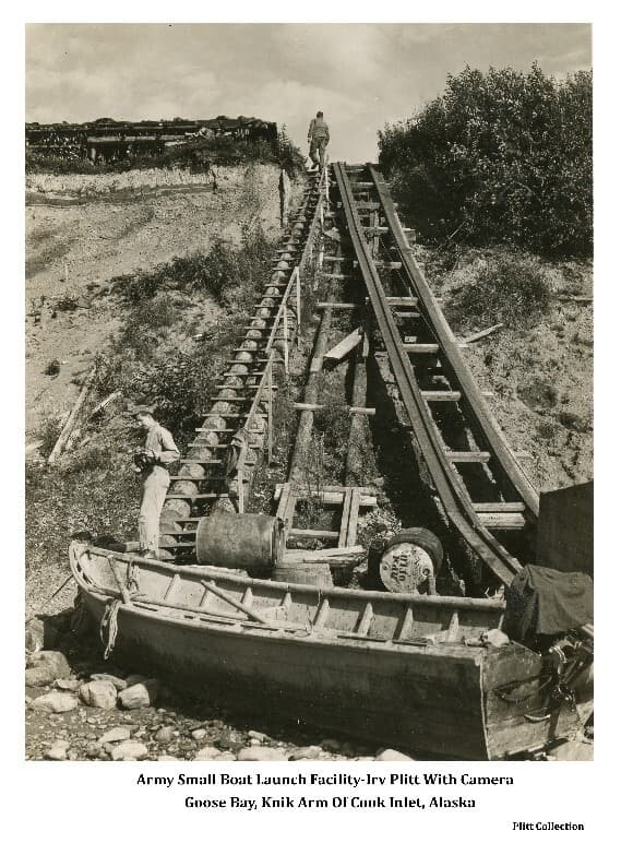 Image shows a small boat launch facility at the army fish smoking facility at Goose Bay. A wooden skiff with outboard motor and several barrels are in foreground at the base of a bluff. Stairs and slide rails rise from the beach to the top of the bluff.  The fish drying rack is visible on top of the bluff. Three soldiers are evident: one at the bottom of the stairs holding a camera is identified as Irv Plitt, one is at the top of the stairs & one is by the drying rack viewing the bay through a telescope identified as having been captured from the Japanese at Atu Island. Soil and gravel stratigraphy of the bluff is evident below the drying rack.
