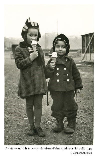 "Image is of two children, identified as Arleta Goodrich and Davy Harrison, standing in a Palmer gravel street eating ice cream cones. Part of a building, automobiles and mountains are visible behind. Photo was taken by a visiting soldier who failed to get names of the children. Later, wanting to give the photo to their family, he enclosed it in a large envelope with a letter, taped a copy of the photo on the outside to serve as the addressee ""in care of Community Center Post Office, Matanuska Valley, Alaska"". It was delivered with no problem."