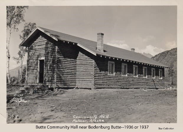Image shows the front and south side of the log community hall constructed soon after the Matanuska Colonists settled the area around the Bodenburg Butte. Two concrete chimneys are in evidence. A portion of the Butte is visible behind the building. This image is on a commercial post card.
