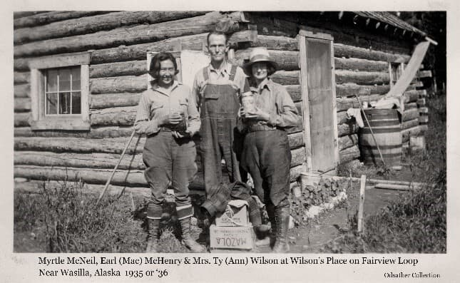 Image shows a man and two women, identified from left as Myrtle McNeil, Earl (Mac) McHenry, and Ann Wilson. They are standing in front of the Wilson homestead cabin. The women hold jars of preserves. A rain trough and water barrel are visible by the front door. The Wilson and McHenry homesteads were located nearby in the Fairview area south of Wasilla.