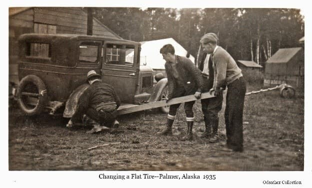 Image shows a man squatting beside the rear wheel of an old car while three young men look on. Two of the men lean on a wood beam as a lever to raise the car so the tire can be changed. A spare tire is attached to the back of the car. Part of a wooden building and two tents and another small building are visible behind the car with trees beyond. The man in the light sweater is identified as Louis Odsather.