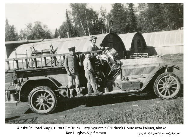 Image is of a man, identified as Ken Hughes, and two young boys on an old fire truck, identified as Alaska Railroad Surplus 1909 Fire Truck vintage. Setting is in front of several Quonset Huts on the Lazy Mountain Children's Home campus. Birch and spruce forest forms the backdrop.