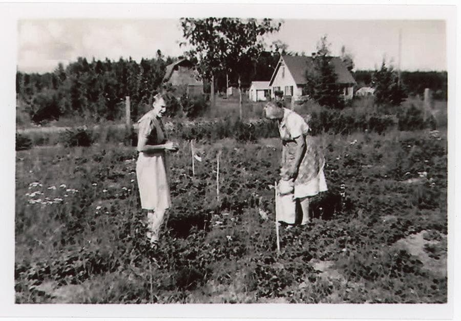Image shows two women and small child standing in a garden with a Colony farmstead behind them and forest beyond.