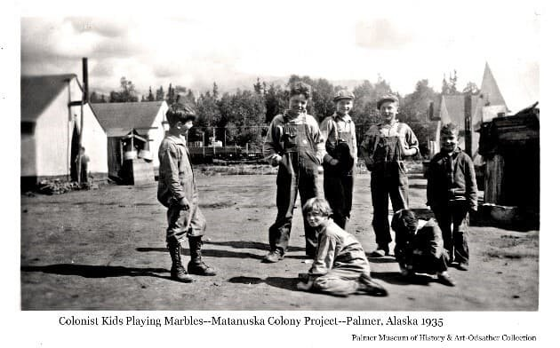 """Image shows a group of children gathered around a game of marbles in the dirt street between Colony tents. Another child stands at the entry to one of the tents. A rail car is visible on the tracks in the background with forest beyond, This appears to be in the original """"Tent City"""" or Camp #1 in Palmer."""