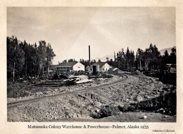 Image shows railroad tracks leading to the northwest aspects of the Powerhouse and the Warehouse. A fuel tank stands next to the tracks. Lumber, poles and gravel are piled on the right-of-way. Trees frame the clearing and mountains are visible in background.