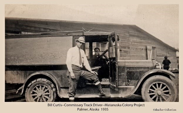Image shows a man, identified as Bill Curtis, standing beside what is identified as the delivery truck for the Colony Commissary. An unidentified woman looks through the far window of the truck. Another woman is seen walking away to the right. The truck is parked in front of the Commissary building in Palmer.