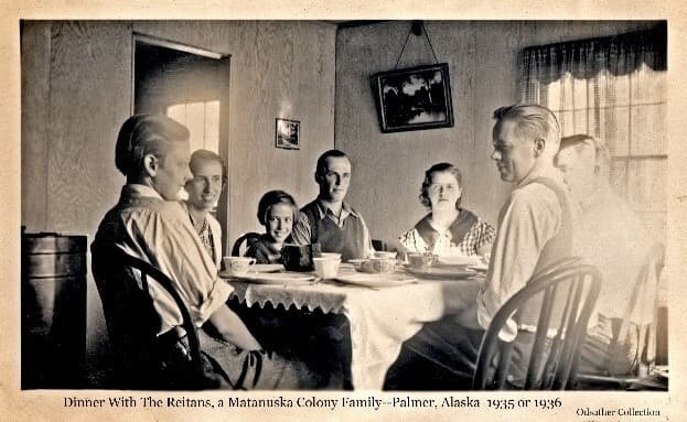 Image shows three men at the dinner table with the Colonist Reitan family, presumably in the Reitan home. Individuals are identified from left as Bill odsather, Alice Reitan, Reitan Daughter, Bernard Reitan, Deana Reitan, Louis Odsather, unidentified.