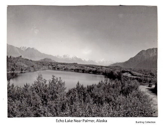 Image shows a view to the East looking across Echo Lake with trees in foreground, a roadway on the right and around the right side of the lake. An automobile is visible on the road in middle ground. Mountains are in background, including the top of Bodenburg Butte and part of Pioneer Peak.