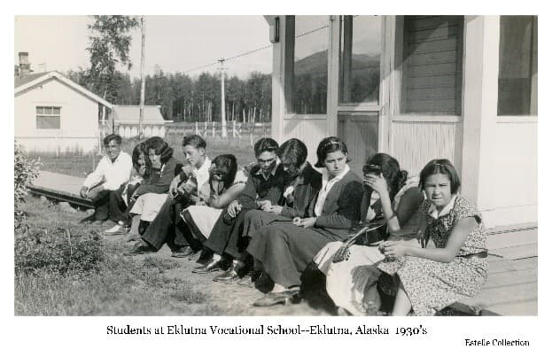 Image shows a group of ten young native men and women students on a sunny day sitting on a boardwalk next to a white frame building. All are nicely dressed, two are holding guitars. Electric lines overhead, power pole, two other buildings and trees are in background.