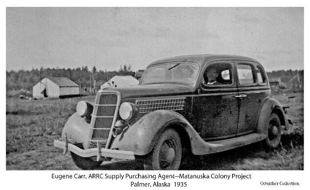 Image shows a four-door sedan with a male driver visible. The driver is identified as Eugene Carr, ARRC Supply Purchasing Agent, per identifying note on a similar photo in the Nichols Collection. Another person is slightly visible in the passenger seat. Tents are visible behind the car with forest beyond.