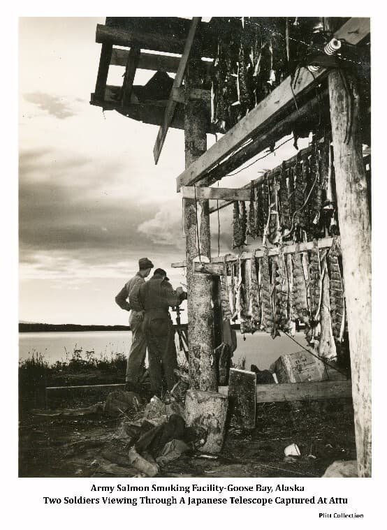 """Note on reverse of photo indicates the image shows soldiers Irv Plitt (left) and another identified as """"Glass"""", standing next to the salmon drying facility at Goose Bay and viewing the bay through a Japanese telescope captured at Atu Island."""