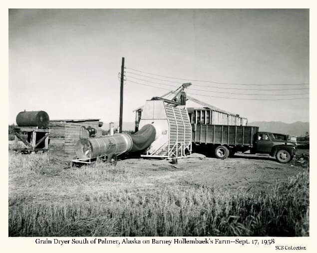 Image shows a collection of structures including a large metal container with an exhaust tube and fan. A high-sided truck is backed up to the structures. A fuel barrel on a stand is evident, as is a power pole and power lines near a wooden shed. Location is identified as the Barney Hollembaek farm south of Palmer. Mountains are in background.