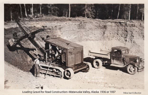 Image shows a power shovel excavating gravel from within a gravel pit. An empty dump truck is parked next to the shovel. A man stands next to the power shovel and another man can be seen in the cab operating the machine. Sand and gravel seams are visible in the pit bank behind the equipment and forest trees are beyond the pit. Hewitt's inscription is visible on the front of the image.