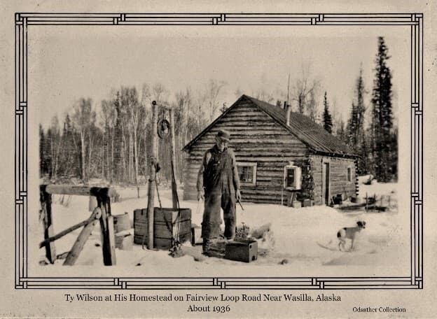 Image shows a man, identified as homesteader Ty Wilson, standing by his well. His log cabin is behind him with trees beyond. A small dog is nearby. Wilson's homestead was on Fairview Loop south of Wasilla.