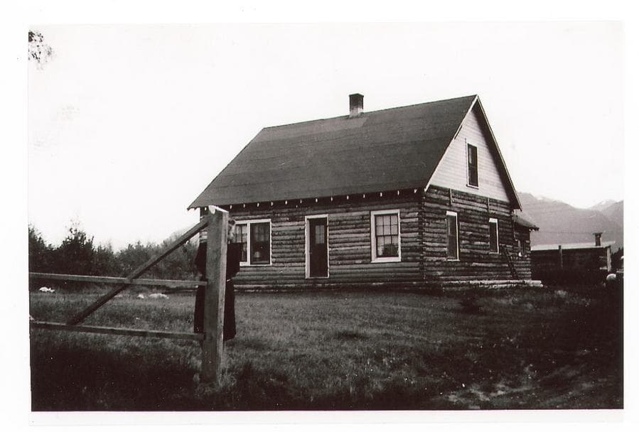 Image is a summer view of a log house with a gate post and rail fence in foreground. A woman appears to stand behind the gate post. An outbuilding and part of a car are visible in middle ground, trees and mountains are evident beyond. This appears to be the north side of House#3.