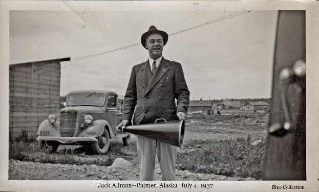 Image shows Jack Allman in suit jacket, tie & hat holding a megaphone. A pickup truck and wood wall of a small building are behind him in the foreground with community building beyond. The megaphone indicates he likely had a prominent role in the 4-of-July events of the day.