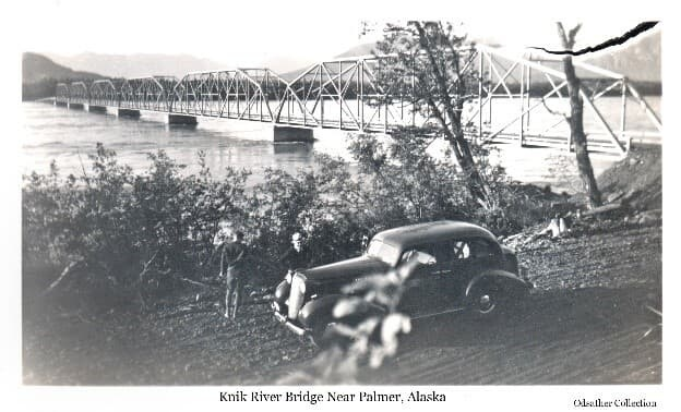 Image shows a four-door sedan parked on the gravel roadside with two men standing nearby. The new bridge over Knik River is prominent behind them. A portion of Bodenburg Butte is visible in the background.