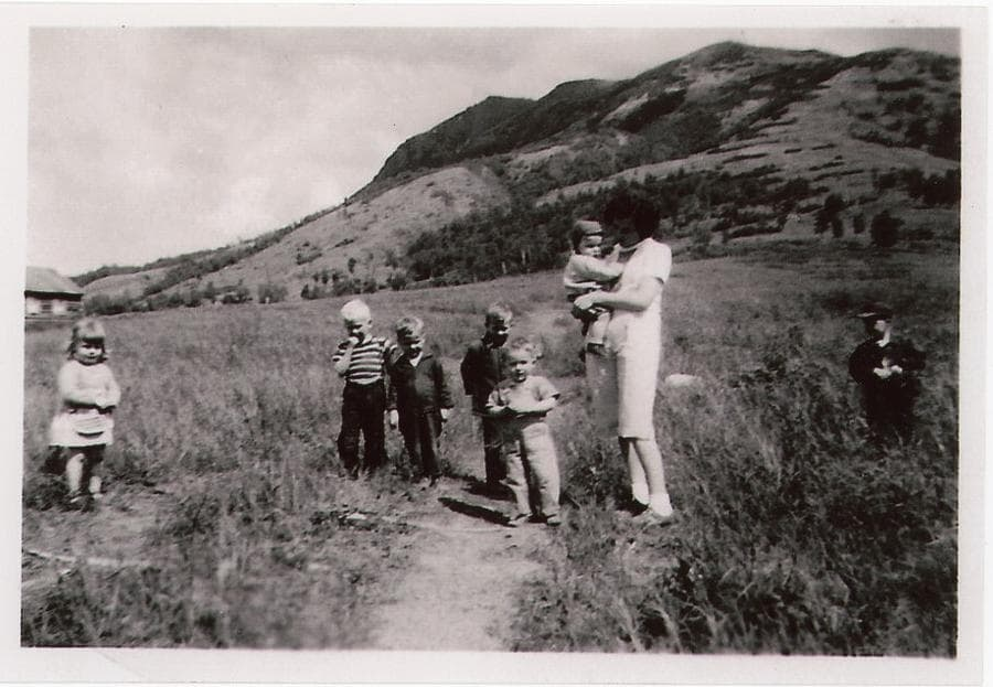 Image shows a summer view of a woman and seven small children standing at the trail near the foot of Lazy Mountain. The slope up the mountain to the peak is prominent in back ground, a portion of a cabin is evident in middle ground. Portions of the trail across the cleared field are evident.