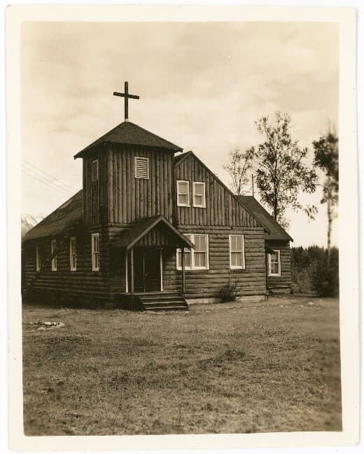 Image is of the front (west side) of the log Lutheran church with grass expanse in front and birch trees beyond.