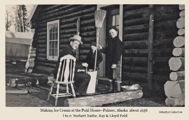 Image shows a man, identified as Norbert Nathe, sitting in a fancy wood chair and turning the handle of an ice cream churn while two children, identified as Lloyd Puhl holding a broom, and Ray Puhl looking on and assisting. They are at the front of the Puhl's house. A tent is visible in background.