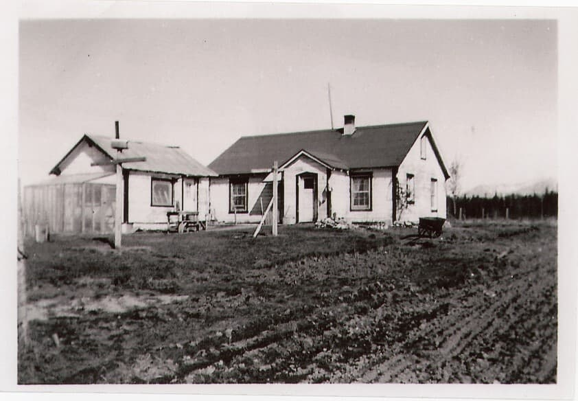 Image shows a white house and small white outbuilding with a greenhouse attached, clothesline posts adjacent, tilled ground in foreground, forest and mountains in background.