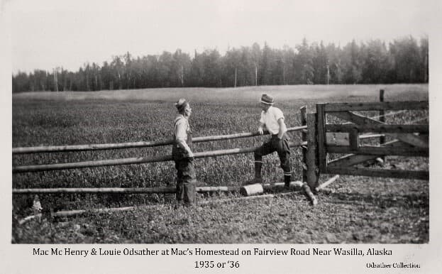"""Image shows two men, identified from left as """"Mac"""" McHenry and Louis Odsather, standing at a rail fence looking over Mac's homestead grain field. A wood Plank Gate is at right. Beyond the field is unbroken forest."""