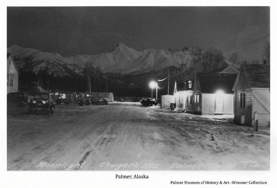 "Image is an east-facing night view along what was called ""Market Street"" in the Community Center of Palmer. A street light and business lights are prominent, the moon furnishing over-all illumination. The Trading Post and Barbershop are prominent at right, the Creamery is partly visible at left. Several cars are evident on the street and busses are parked at left. Lazy Mountain and Byers Peak are prominent in background."