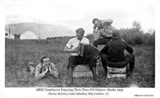 Image shows four men, identified from left as Jimmy McCann, Louis Odsather, Skip Cowden and unidentified. Three are sitting on wooden boxes and one lies on the ground while Odsather is playing an accordion. Tents are visible in background.