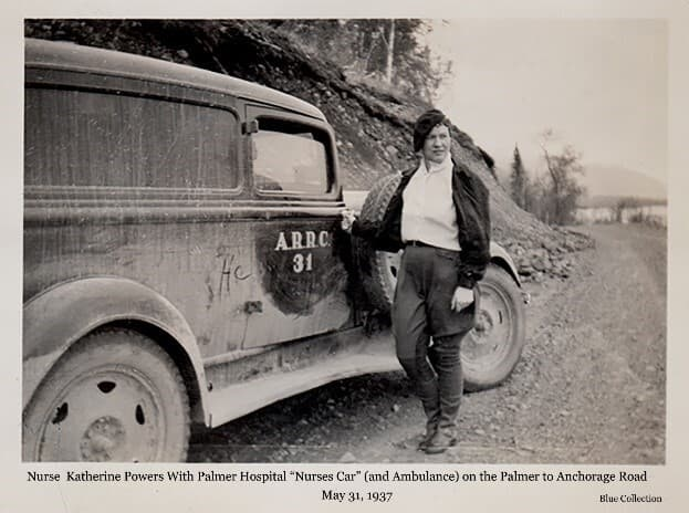 "Image shows Palmer hospital nurse Katherine Powers standing beside the ""Nurses Car"" and ambulance parked on the gravel Palmer to Anchorage Road. The location is likely just south of the Knik River Bridge based on other associated photos in the collection. The vehicle is identified as ""ARRC 31."""