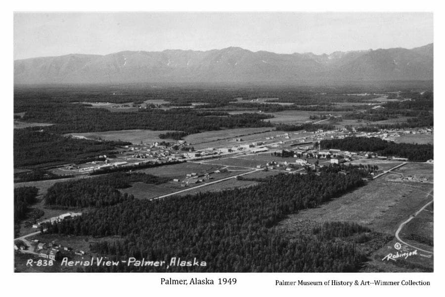 Image is an aerial oblique looking northwest across the city of Palmer, including farms, fields, forest, roads and Talkeetna Mountains in background. Buildings and the Valley Fairgrounds are evident.