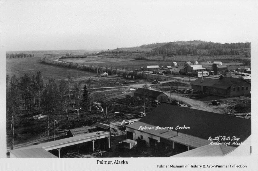 Image is a summer low oblique view across the Co-op garage and storage yard, including the Railroad depot, the south end of Palmer business district, fields, hill and forest beyond.