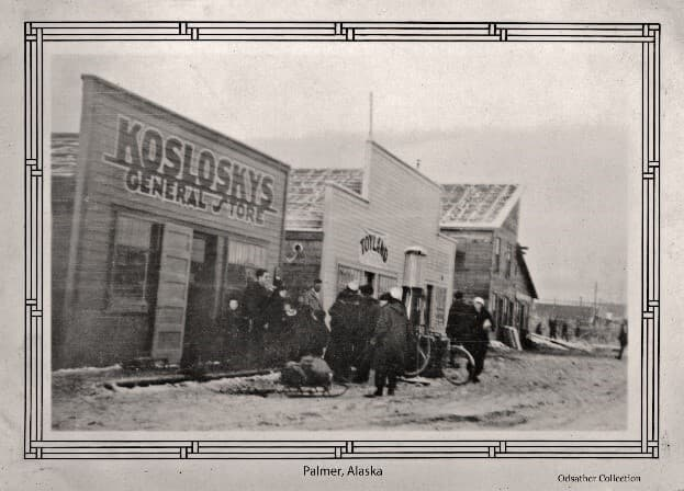 """Image is a north view of Palmer main street with people on the street front. Identified is """"Koslosky's General Store"""", """"Toyland"""" and Horton's buildings. A gas pump is visible in front of Koslosky's. Children's sleds are visible as is a bicycle."""