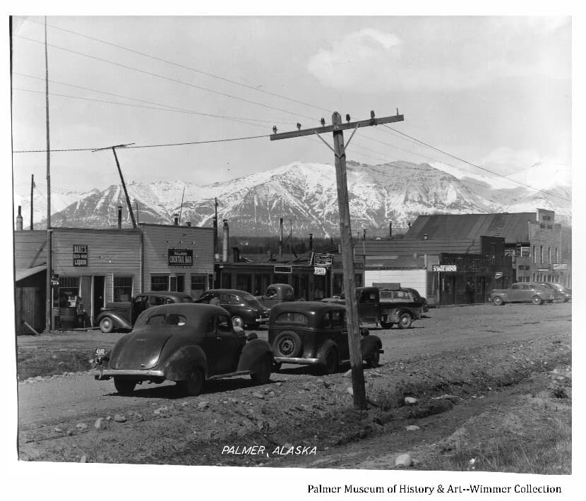 Image shows a spring view of Palmer's gravel street in foreground with numerous buildings in middle ground. Several buildings exhibit business signs. Two cars are parked in foreground and several cars are parked in front of buildings.  A telephone/telegraph pole is prominent in center foreground. Several men are evident near buildings. Snow-clad Talkeetna Mountains are in background.
