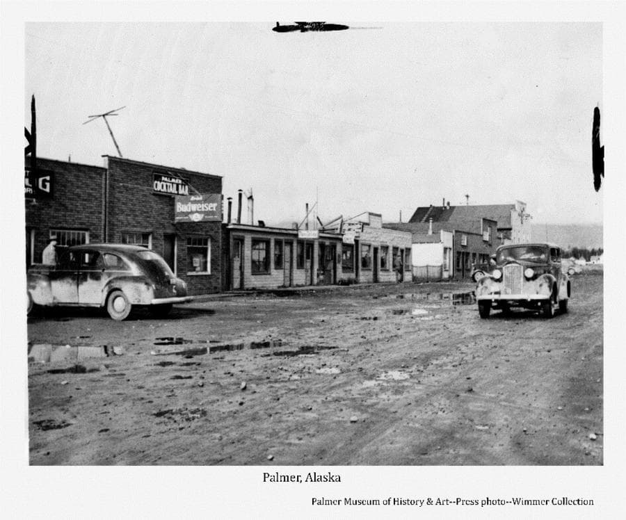 Image shows a view of Palmer's gravel street with water puddles in foreground and numerous buildings in middle ground. Several buildings exhibit business signs. Two cars are in foreground and other cars are visible parked in front of buildings beyond. A man is evident on the sidewalk. Newspaper crop marks are apparent on photo edges.