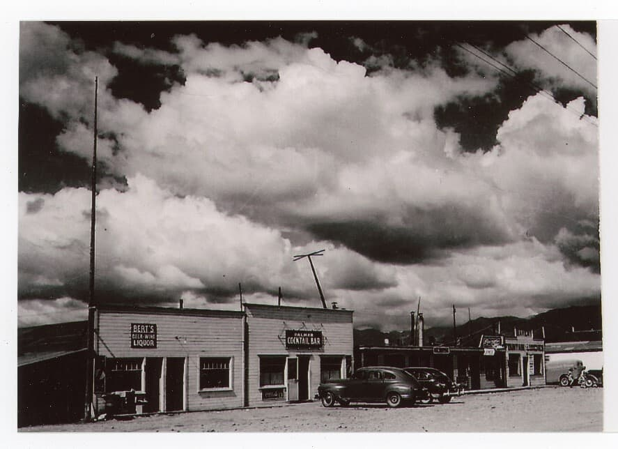 Image is a street scene of downtown Palmer businesses with vehicles parked in front. Numerous signs are evident and a variety of vehicles. Gravel street is in foreground, white clouds overhead.