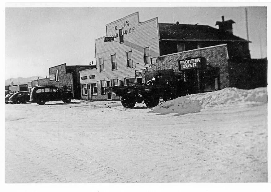 Image is of downtown Palmer storefronts and automobiles parked in front on a snow-covered street. Business signs are visable.