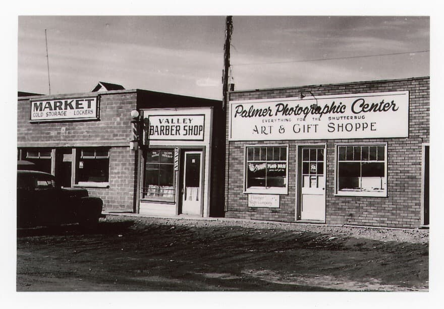 Image is of downtown Palmer storefronts and an automobile parked in front. Business signs are prominent for a Market, Barber Shop & Palmer Photographic Center.