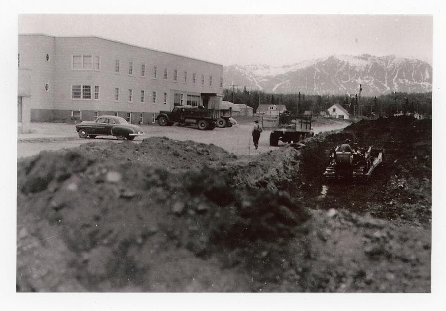 """Image shows a springtime scene of excavation for construction of the Palmer Drug Store with a pile of gravel in foreground & a """"cat"""" in the hole pushing out more. The Valley Hotel is prominent across the street. Cars & trucks are parked along the street. A man is on the """"cat"""" and another is walking in the street. Houses & a Quonset Hut are visible in middle ground with forest and snow-laced Talkeetna Mountains beyond."""