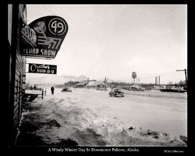 Image shows a winter scene looking north along Alaska Street from the sidewalk in front of the 49 Club Bar. The bar sign is prominent as is a sign for Charlie's Bar B-Q. Blowing snow is evident. Plowed snow berm at the sidewalk is prominent. Three people are visible and several automobiles. The railroad depot is in middle ground as is the co-op garage, water tower, powerhouse, and a flatcar on the tracks. Talkeetna Mountains are in background.