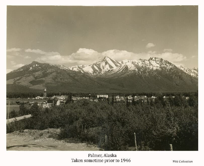 Image shows the town of Palmer viewed from Bugge's Hill looking east. Gravel road bed and trees in foreground, snow-capped mountains with clouds overhead in background. Lazy Mountain and Byer's Peak are evident. This photo was probably taken the same day as the one coded Man@1-Plt in the Plitt collection.