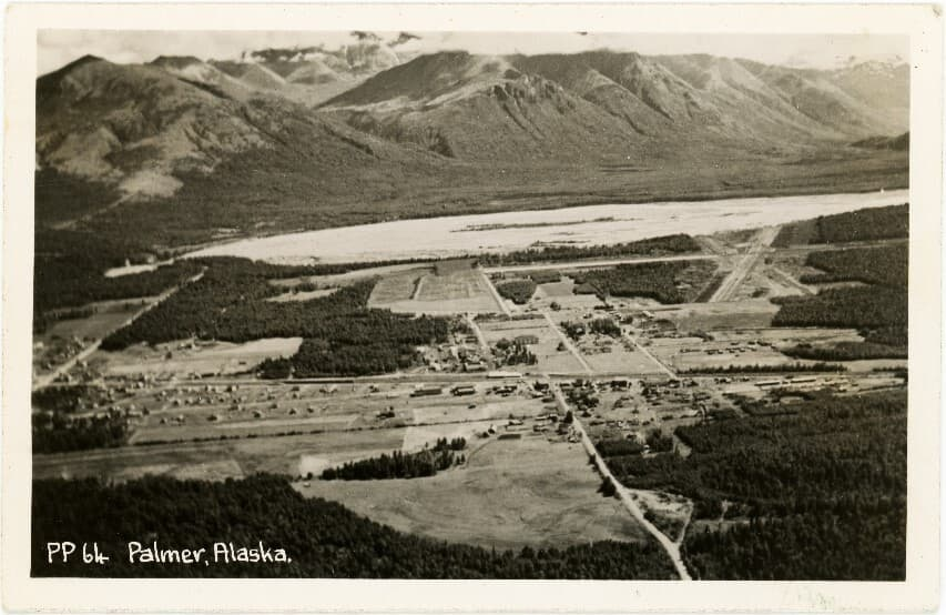 Image is an east-facing aerial oblique of Palmer and surrounding area including John Bugge's homestead, the Palmer airport, Matanuska River and mountains beyond, including Lazy Mountain.