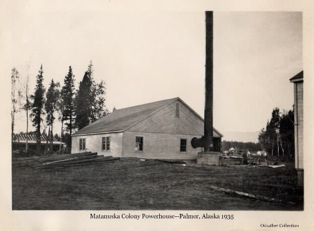 Image shows the southeast view of the community Powerhouse, exterior construction complete with smokestack installed. The railroad depot under construction is visible beyond, as are tents across the tracks. The southwest corner of the warehouse is visible.