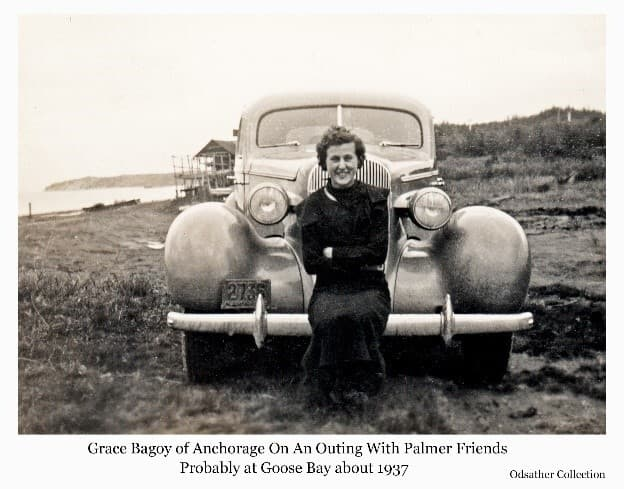 Image is of a young woman, identified as Grace Bagoy of Anchorage, sitting on the bumper of an unidentified make of automobile. A water body is visible in background with a small open boat on the shore next to a building that appears to be a smokehouse. Contemporary photos in the collection support the assumption that this photo was made on a group outing to the Goose Bay area.