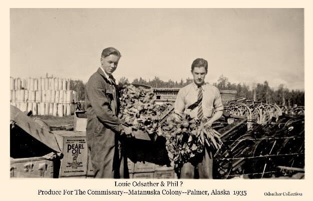 Image shows two men, Louis Odsather on left, the other identified only as Phil, hold vegetables likely destined for sale at the Commissary. Colony equipment and supplies are piled behind the men.