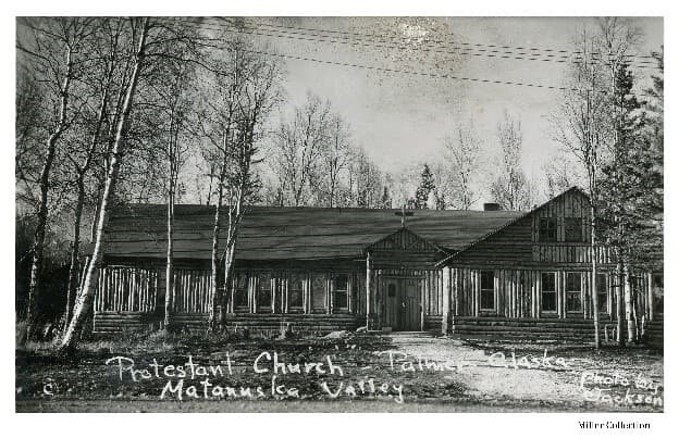 """Image shows the north side of a log church, identified as the Protestant Church, also commonly referred to as the Community (Presbyterian) Church or the """"Church of a Thousand Trees"""", in Palmer, Alaska. Trees are evident in front and beyond and power lines overhead."""