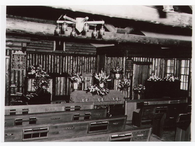 Image is of the interior of the Palmer Protestant Church, unoccupied pews in foreground, a closed casket in front with floral bouquets prominent.