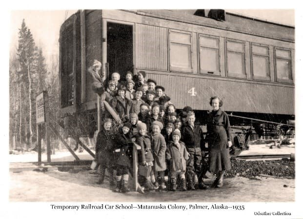 Image shows a group of young children and a woman assembled on steps up to the doorway of a railroad car. This is a class of students and their teacher attending school in the temporary facility of the rail car while the permanent Palmer school building was being built.