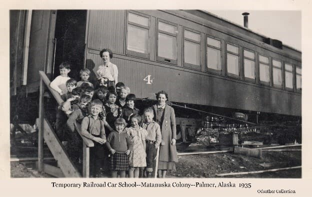 Image shows a group of young children and two women assembled on steps up to the doorway of a railroad car. This is a class of students and their teachers attending school in the temporary facility of the rail car while permanent Palmer school building was being built.