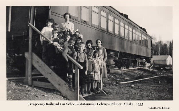 Image shows a group of young children and two women assembled on steps up to the doorway of a railroad car. This is a class of students and their teachers attending school in the temporary facility of the rail car while the permanent Palmer school building was being built. A typical colony tent is visible in background.
