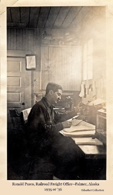 Image shows a man, identified as Ronald Pasco, railroad freight agent for Palmer, in the Railroad freight office in Palmer.